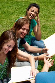 Three Austin TX students are savoring a few moments on the campus lawn